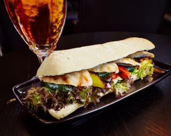 сэндвич с кусочками курицы, салатом, цукини и помидорами на черной тарелке на столе, рядом бокал пива