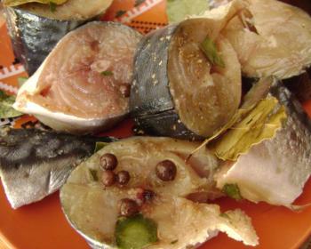 кусочки скумбрии сухого посола со специями на оранжевой тарелке