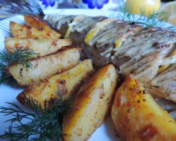 запеченная скумбрия с дольками лимона, политая майонезом, с кусочками картофеля и веточками укропа на белой плоской тарелке