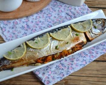 скумбрия, запеченная целиком с луком и морковью, лежит на длинной белой тарелке, сверху рыба украшена дольками лимона