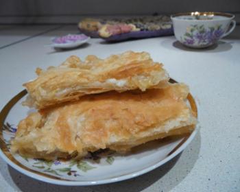 кусочки слоеного пирога с творогом в маленькой тарелочке на столе