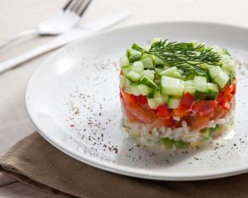 слоеный салат из слабосоленой семги, красного сладкого перца, вареного риса и свежего огурца, украшенный веточкой укропа, на белой плоской тарелке, присыпанной специями, на столе