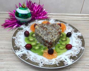 сочиво из риса с сухофруктами, урашенное дольками киви, мандарина и виноградом, на тарелке, елечная игрушка и мишура на столе