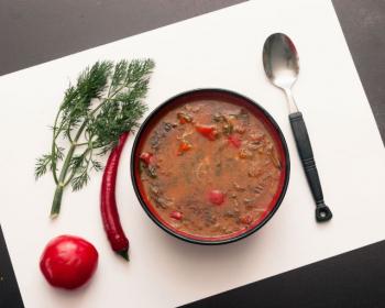 тарелка с солянкой по-грузински на столе на белой салфетке, рядом лежит ложка, помидор, жгучий перец и веточка укропа