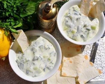 две глубокие белые тарелочки с соусом Цацики и лавашом, рядом лежит пучок зелени, лимон, столовая ложка и золотистая баночка