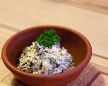 соус цахтон из кусочков маринованного острого перца с листьями со сметаной и зеленью в коричневой тарелке на столе
