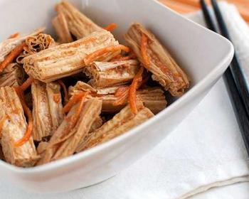 спаржа по-корейски с морковью и специями в белой квадратной пиале на столе, рядом палочки для еды