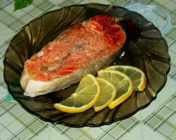 стейк из форели, запеченный в фольге, с лимоном на широкой черной тарелке на столе