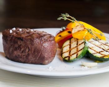 говяжий стейк с жареными кусочками цукини, желтого сладкого перца и помидоров с веточкой розмарина на белой плоской тарелке на столе