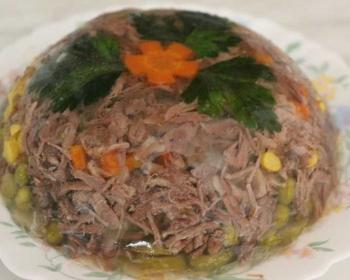 тарелка со студнем полукруглой формы из говядины с добавлением моркови, горошка и листьев петрушки