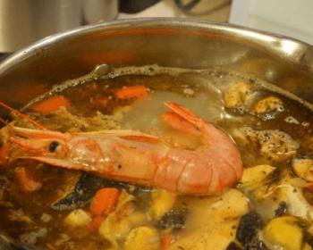 суп буйабес из морепродуктов в кастрюле, одна большая креветка вверху