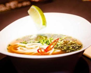 суп Фо Бо в тарелке, украшенной долькой лайма