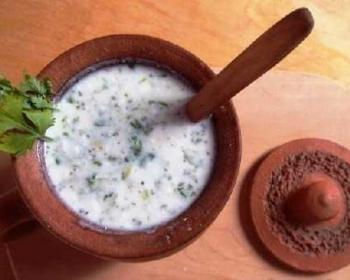 суп из мацони с зеленью в глиняном горшочке с ложкой на разделочной доске на столе