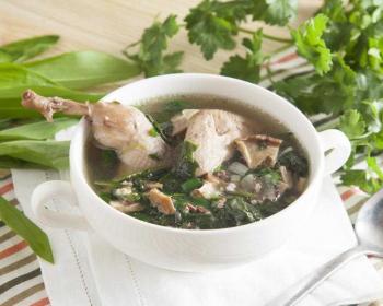 глубокая тарелка с супом из перепелов с добавлением большого количества зелени, на фоне пучки свежей зелени