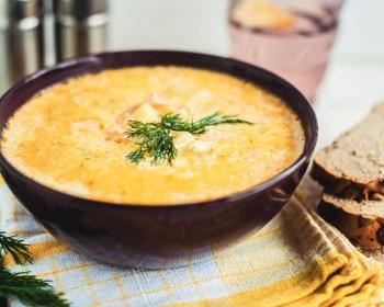 суп норвежский с семгой, украшенный веточками свежего укропа, на льняной салфетке на кухонном столе, на фоне кусочки хлеба
