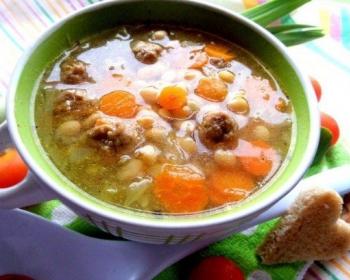 суп с фрикадельками, фасолью, морковью и луком в зеленой тарелке на столе