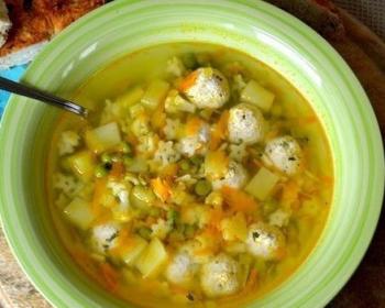 суп с фрикадельками, кусочками картофеля и моркови, зеленым горошком и макаронами в глубокой зеленой тарелке с ложкой на круглой деревянной разделочной доске на столе