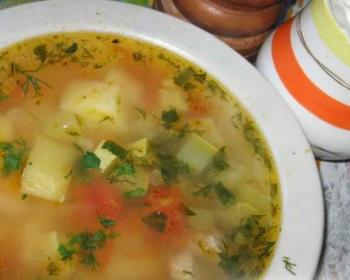 суп с кусочками картофеля, кабачков, помидоров, лука и моркови, посыпанный рубленой зеленью, в глубокой белой тарелке на столе, застеленном скатертью