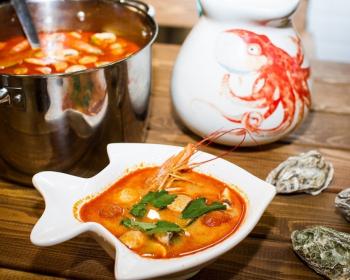 суп Том Ям с креветками и кальмарами в тарелке в виде рыбки, на фоне кастрюля с супом