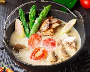 котелок супа Том Кха с курицей, шампиньонами, помидорами черри, луком пореем и спаржей на столе