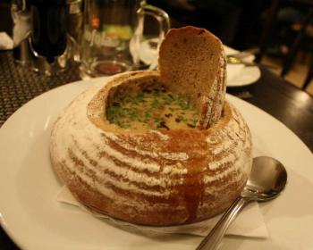 чешский суп с говядиной в ржаном хлебе на тарелке