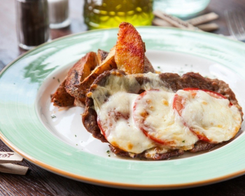 запеченные кусочки свинины, с кружочками помидоров с сыром и картофелем на плоской тарелке на столе