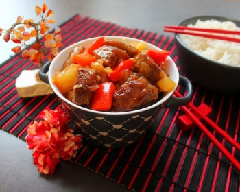 свинина по-китайски с овощами в тарелочке, рядом рис в миске и палочки на столе, застеленном деревянным ковриком