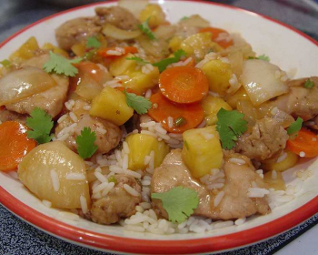 свинина по-тайски с рисом и овощами в тарелке на столе
