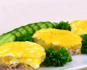 три кусочка свинины, запеченной с ананасом и сыром, лежат на овальной тарелке, украшенные веточками зелени, на краю тарелки лежат нарезанные кольцами свежие огурцы