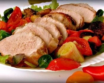 ломтики свинины, запеченной с овощами, на тарелке