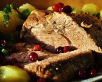 свинина, запеченная в мультиварке, лежит на блюде, сверху лежат ягоды клюквы, возле мяса лежит вареный картофель, присыпанный свежей зеленью
