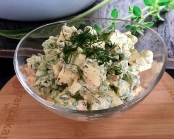 на столе в прозрачной пиале лежит сыроедческий салат оливье с каперсами