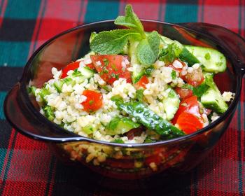 табуле с булгуром, овощами и зеленью в глубокой тарелке на столе, застеленном красно-черной клетчатой скатертью