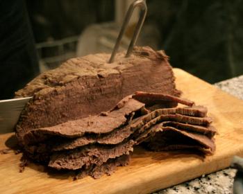 тафельшпиц из говядины, нарезанный ломтиками, на разделочной доске