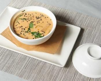 тайский суп с кокосовым молоком в глубокой белой тарелке на столе