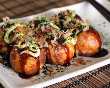 такояки из жареных шариков с начинкой внутри, смазанных соусом с зеленью, на белой тарелке на столе, застеленном деревянным ковриком