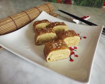 японское блюдо тамагояки в квадратной тарелке на столе