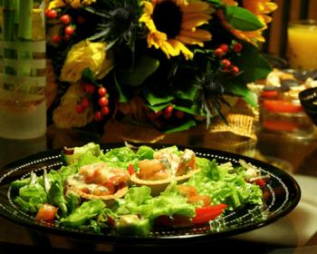 на круглой черной тарелке лежат свежие листья салата, дольки помидора и две тарталетки с креветками, рядом стоит ваза с цветами