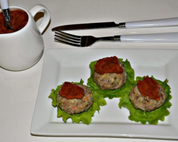 на белой квадратной тарелке на листьях салата лежат три тефтели, рядом вилка и нож и большая соусница с соусом