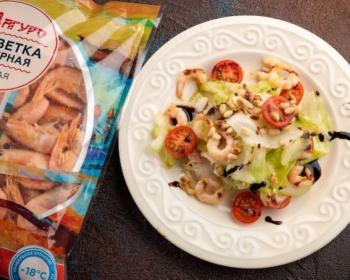 теплый салат с креветками, помидрами, зеленью и кедровыми орешками в белой тарелке, рядом пачка замороженных креветок
