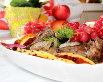 теплый салат с куриной печенью, яблоками и луком, украшенный зеленью, веточкой красной смородины, в блюде на столе, яблоки на фоне