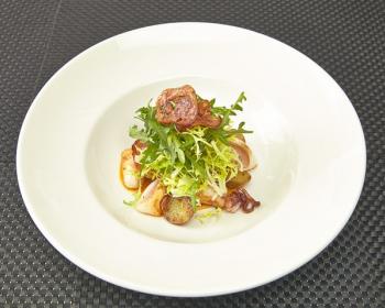 салат с морепродуктами, жареной колбасой и рукколой на белой плоской тарелке на столе