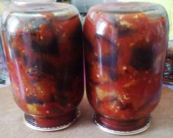 кусочки баклажанов со сладким перцем в томатном соке в двух стеклянных законсервированных банках на столе