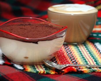 слоеный тирамису с маскарпоне, присыпанный какао, в стеклянной миске на столе, застеленном тканью, рядом ложка