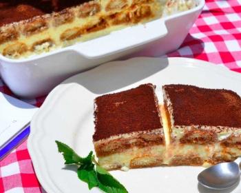 прямоугольный кусочек тирамису с творогом, разрезанный пополам, лежит на белой тарелке, рядом чайная ложечка, листок свежей мяты, на фоне белая кераммическая форма с десертом