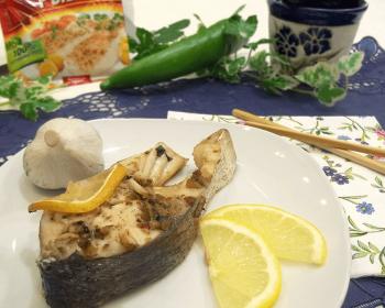 на круглой белой тарелке лежит порционнный кусочек толстолобика, запеченного в духовке, рядом лежат две дольки лимона, головка чеснока, рядом на столе две деревянные палочки