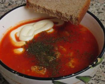 томатный суп с фрикадельками, зеленью и майонезом в супнице с кусочком черного хлеба на кухонном столе