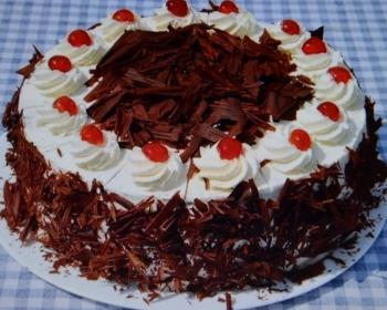 на большом блюде лежит торт черный лес, присыпанный тертым шоколадом, взбитым белым кремом и вишнями
