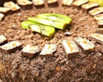 торт из пряников с бананами, сверху присыпанный измельченными пряниками, по кругу лежат кусочки шоколада, в середине изделия лежат три дольки киви