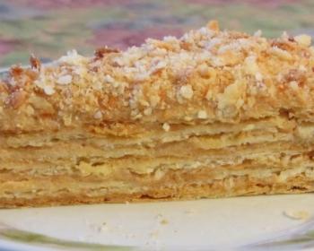 кусок торта из слоеного теста со сгущенкой на белой плоской тарелке